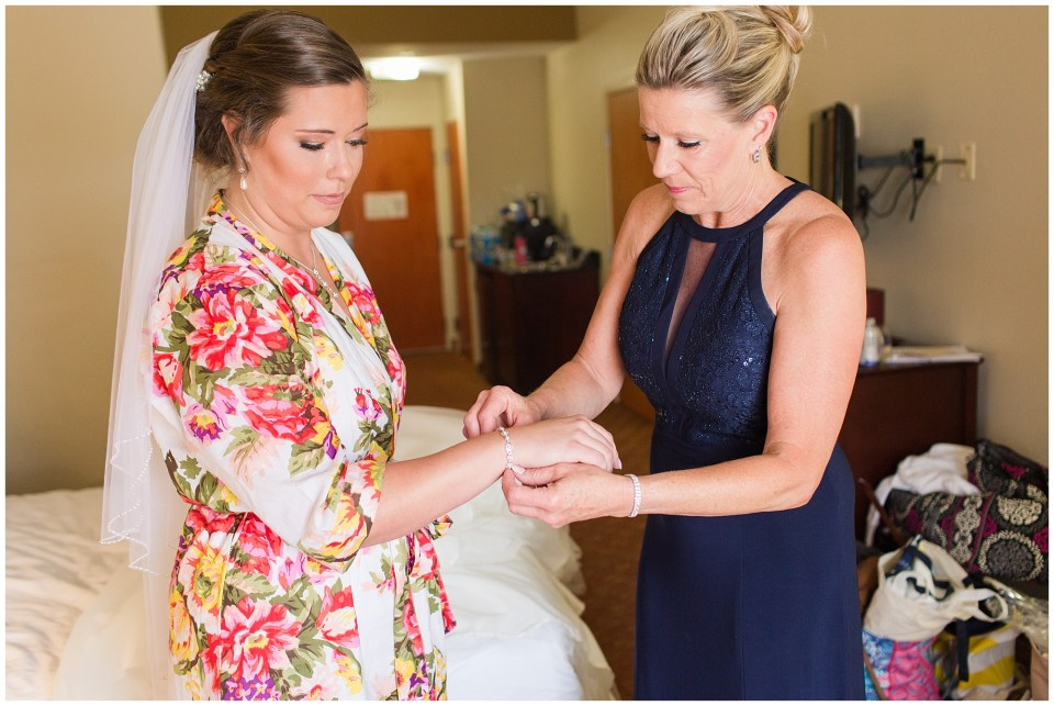 mother of the bride helping bride with bracelet