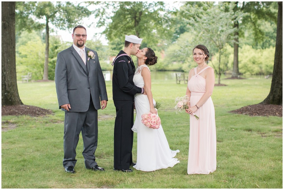 bride and groom kissing by wedding party