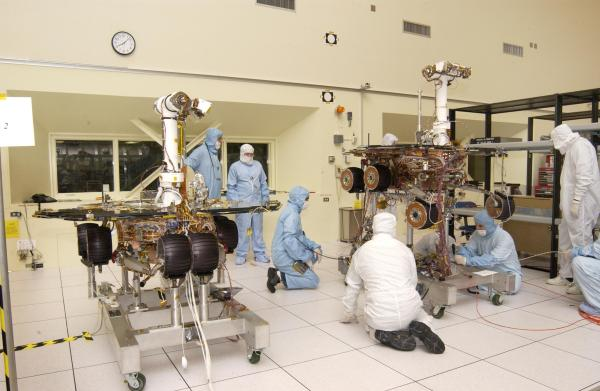 Na 13 let starém záběru z února 2003 vidíme vpravo Spirit a vlevo Opportunity, jak jsou již téměř kompletně připraveni k letu. NASA/JPL