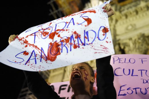 Brazilians protest in front of the Legislative Assembly of Rio de Janeiro (ALERJ) on May 27, 2016, against a gang-rape of a 16-year-old girl.  Brazilian police on Friday were investigating the gang-rape of a 16-year-old girl whose attackers boasted about it by posting an online video of her that has horrified the country. Online social networks erupted with outrage over the video posted on Wednesday featuring the girl naked on a bed and the apparent rapists bragging that she had been raped by more than 30 men. / AFP PHOTO / VANDERLEI ALMEIDA