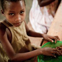 A young African girl in an orphanage looks up from her meal at the dining table.