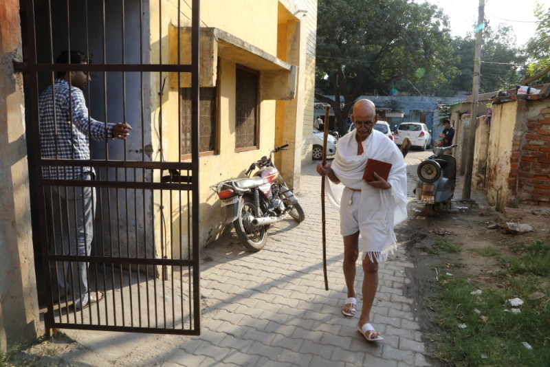 Above - A man looks on as Chaturvedi walks through a street.