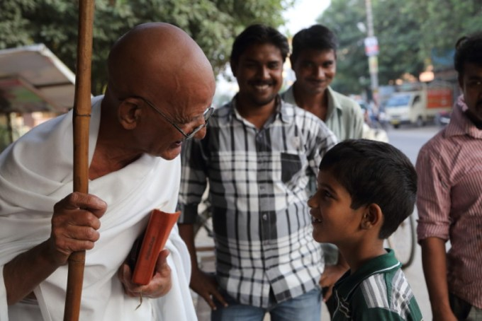 Above - Chaturvedi stops to talk to a child while walking on in a road in Delhi.