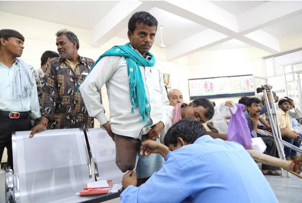 """A man gives measurement for his """"Jaipur Knee"""" prosthetic."""