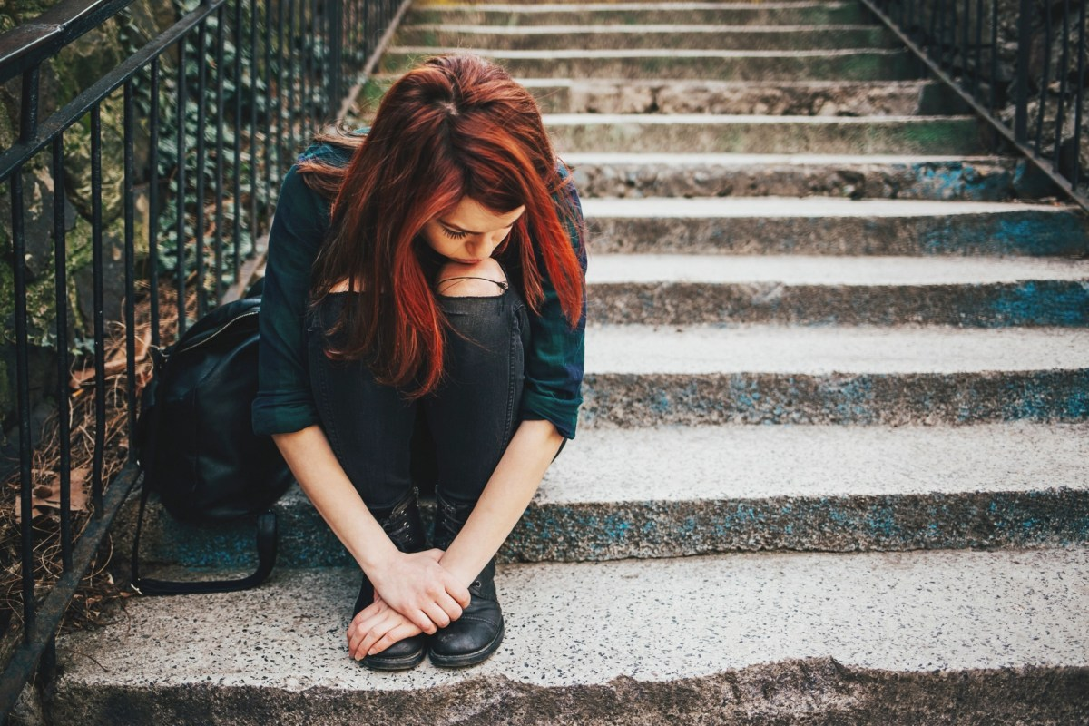 Depressed young woman sitting on stairs outdoors, with copy space