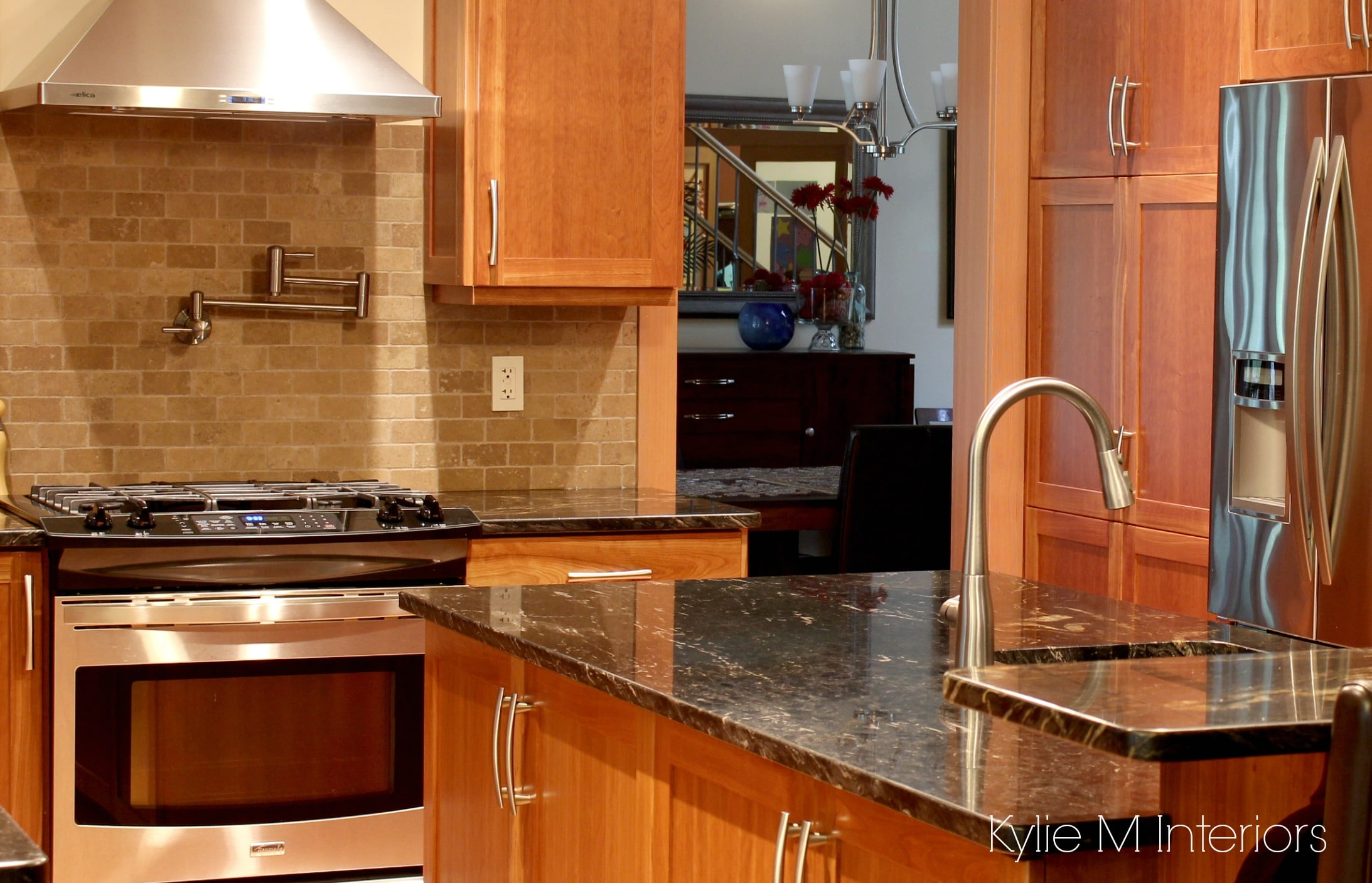 Natural cherry cabinets in kitchen with black granite prep sink pot filler and travertine tile backsplash by Kylie M INteriors
