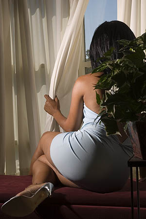 Young black woman watches at window USA