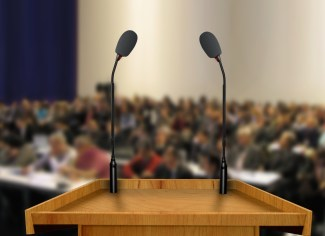Podium with mounted microphones in front of a crowd.