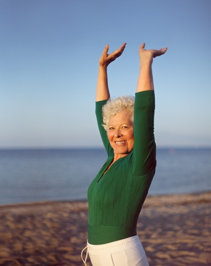 Healthy senior woman practicing yoga on beach