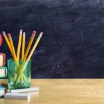 apple on books with pencils and empty blackboard - back to school