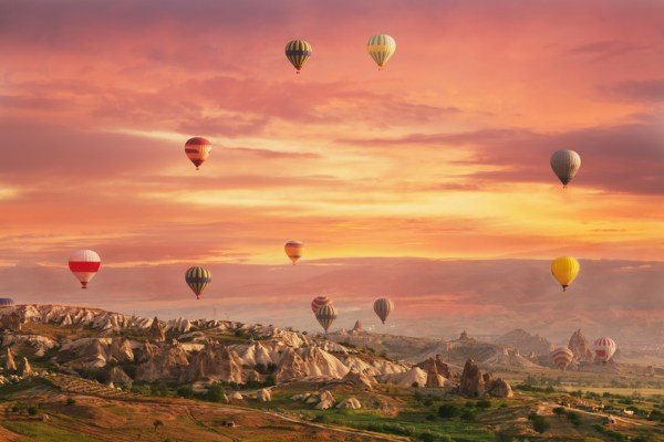 Multi-colored air shata fly over rocks in Cappadocia at sunrise
