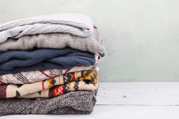 warm sweaters stacked on wooden table