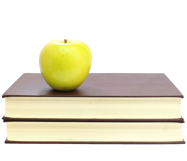 Green apple on stack of book isolated on white background