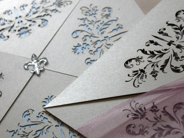 Couture invitations feature a delicate laser cut French pattern - blue and purple