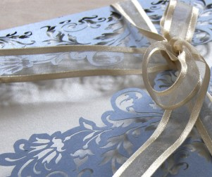 Close up on ribbon of French Flair laser cut wedding invitation