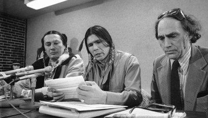 American Indian Movement leader Dennis Banks, center, talks to press conference of his and fellow AIM leader Russell Means, left, attempts to help in food distribution on Wednesday, Feb. 20, 1974 in Minneapolis, Minnesota, as efforts to effect the release of kidnaped Patricia Hearst continue. At right is AIM attorney William Kunstler. (AP Photo/Jim Mone)