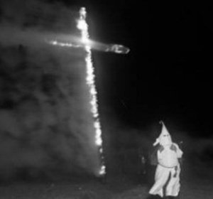 A Ku Klux Klan member burns a cross on Ruby Hill in Denver. (Credit: Wikimedia Commons)