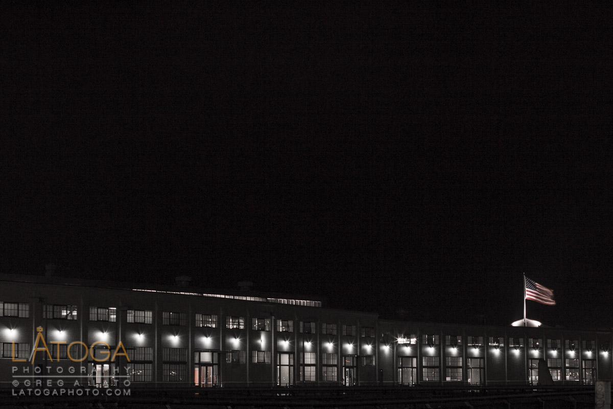 American flag flies over Pier 1, The Embarcadero at night in San Francisco, California.