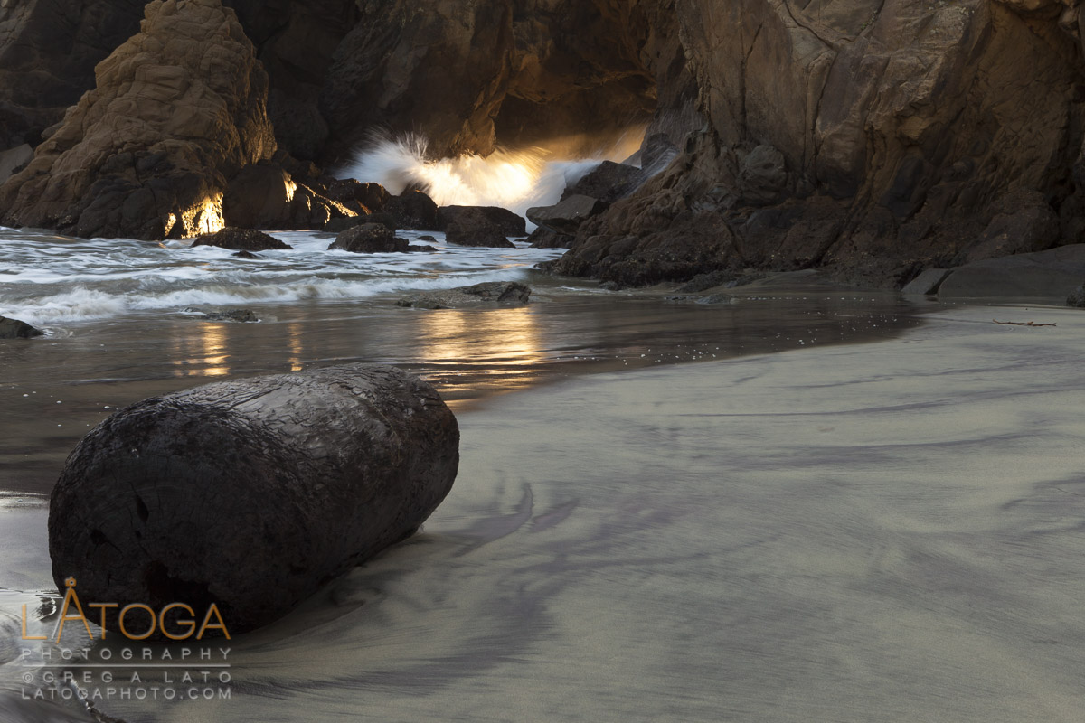 A water soaked log witnesses sunset streaming through a sea arch at Pfeiffer Beach, Big Sur, California.