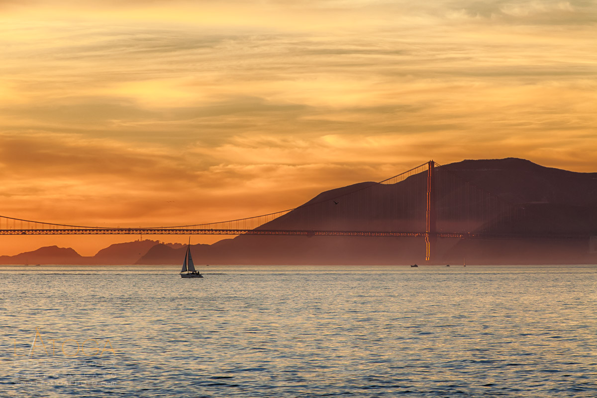 A sailboat crosses San Francisco Bay in front of the Golden Gate Bridge at sunset.