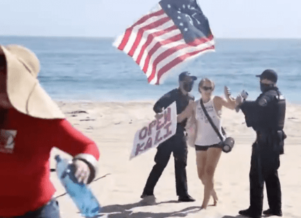 Beachgoers swarm officers trying to arrest woman who walked on the beach in defiance of Newsom's mandate