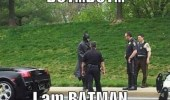 A funny picture of Batman and his black Lamborghini being pulled over by police cops. But I am Batman.