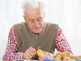 old man peeling potato