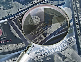 A magnifying glass over $20 notes.