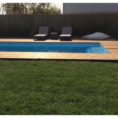 Vue de côté sur la terrasse en pin bombé et la piscine