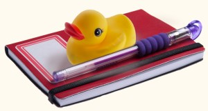 Rubber Ducky Sitting on a Notebook