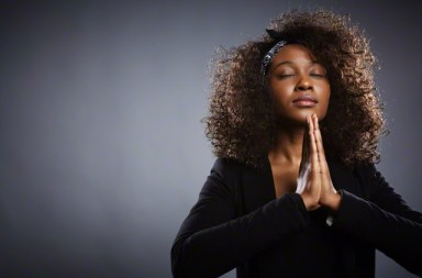 young businesswoman praying --- Image by © Corbis