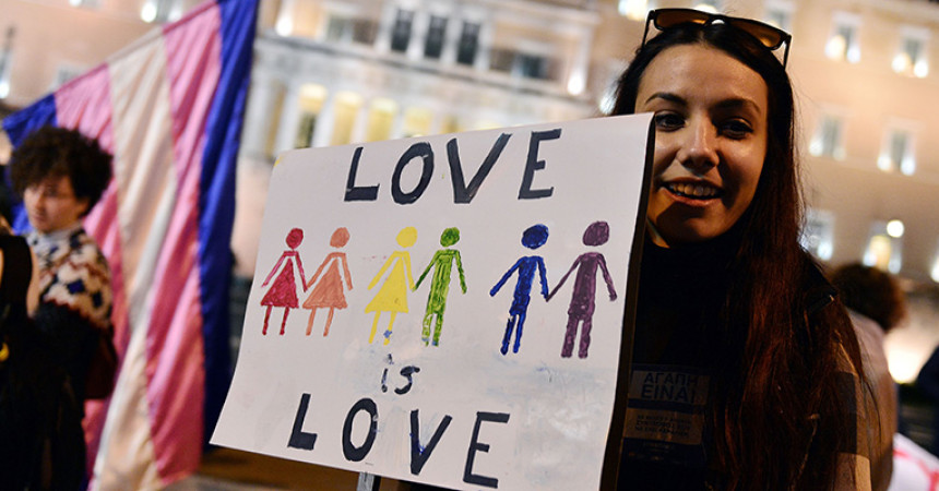 "A woman holds a placard reading ""Love is love"" during a demonstration of gay rights activists and members of the Athens LGBT community outside the Greek parliament in Athens on December 22, 2015 as parliament votes on granting same-sex couples the right to a civil union, despite strong opposition from the influential Orthodox church. Greek government is seeking to meet its obligations after it was condemned for anti-gay discrimination by the European Court of Human Rights in 2013. / AFP / LOUISA GOULIAMAKI        (Photo credit should read LOUISA GOULIAMAKI/AFP/Getty Images)"