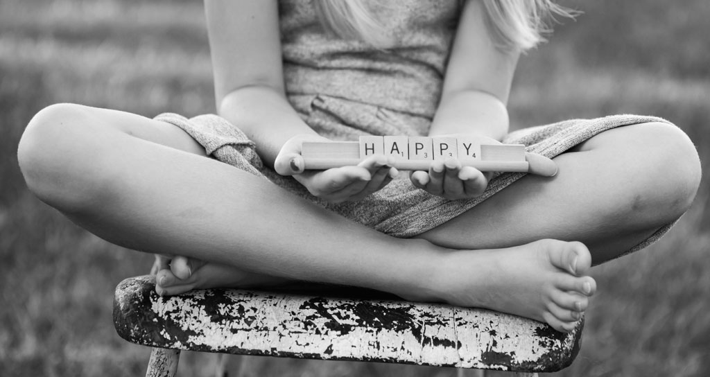 black and white photo of a young girl holding scrabble letters spelling happy - lisa d. photography - phoenix children photographer - scottsdale children photography