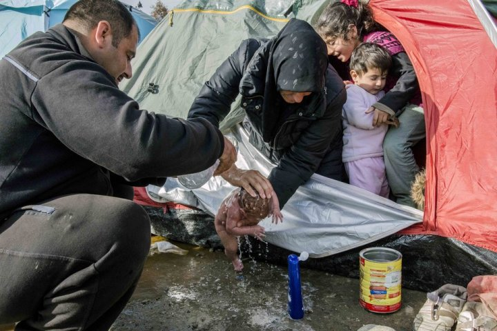 IDOMENI, GREECE - MARCH 6: Refugees wash a new born baby as they stay in tents that they set up in the Idomeni town in Greece, near the Macedonian border on March 6, 2016. (Photo by Iker Pastor/Anadolu Agency/Getty Images)