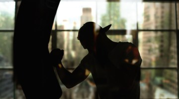 Boxer hits a punching bag against the window, training