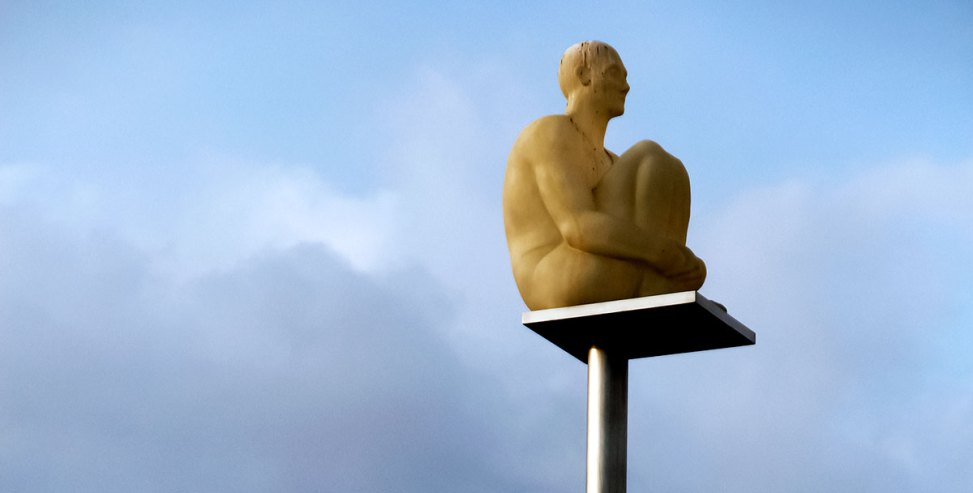 Skulptur av mann sittende på toppen av en stolpe.