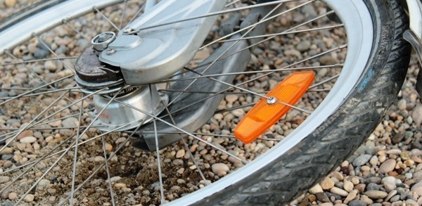 A wheel from a bike shown on the ground next to some pebbles