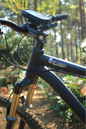 The Voodoo canzo mountain bike showing the front wheel and handlebars with the sun and forest in the background