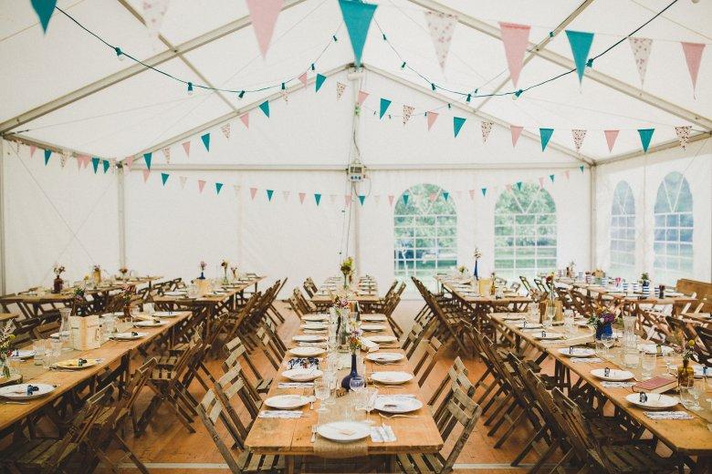 Love & Tralala Mariage champêtre en Dordogne - salle de mariage sous tente avec tables en bois, fagnions et guirlandes guinguette