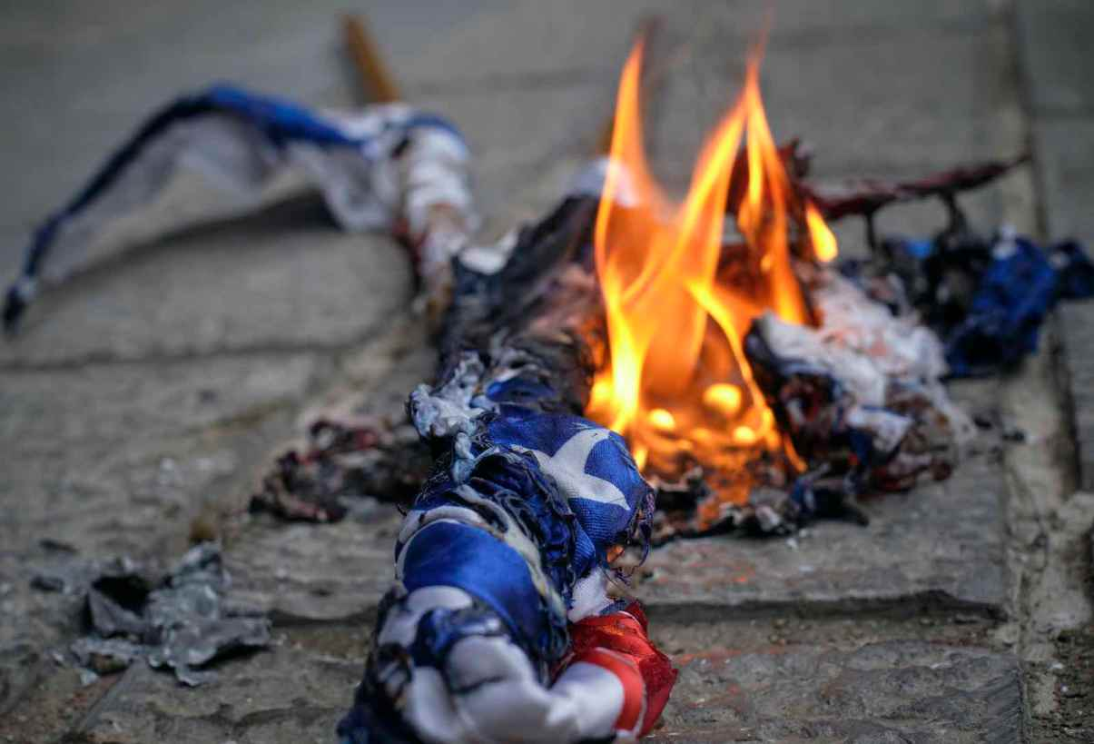 Demonstrators set fire to US and Israel flags outside the Iranian Foreign Ministry in Tehran on 28 November, following the assassination of Mohsen Fakhrizadeh (Morteza Nikoubazl/NurPhoto via Getty Images)