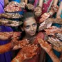 Schoolchildren show their hands decorated with henna paste during a henna competition to mark World Population Day in the western Indian city of Ahmedabad