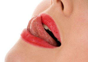 Beautiful woman leaking teeth with tongue close-up