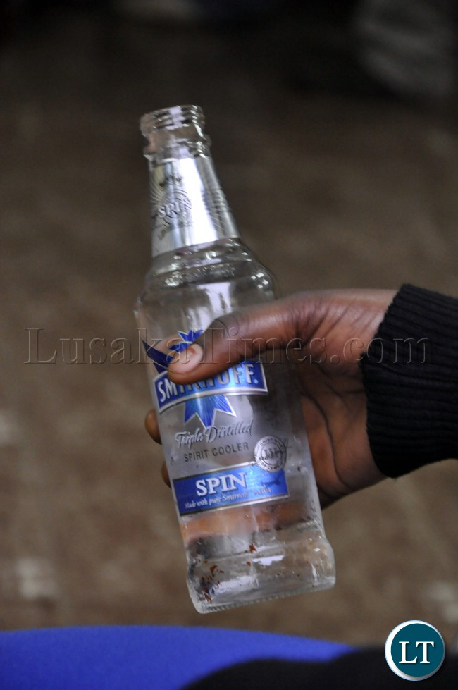 A woman holds a bottle of an alcoholic beverage during the Zambia Bukina Faso match in Lusaka