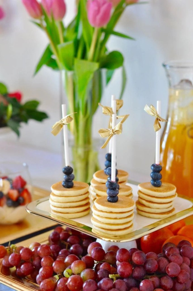 Mini pancakes on a stick for a brunch party. Cute idea!