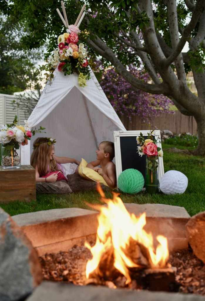Kids boho party outdoors in teepee with flowers