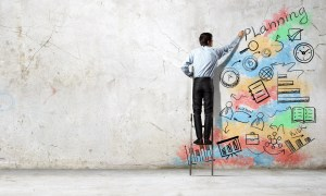 Back view of businessman standing on ladder and drawing sketches on wall
