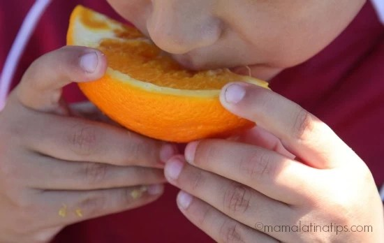 Kid eating an orange after a soccer game by mamalatinatips.com