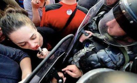 Makedonsk demonstrant bruker et politiskjold som speil for å ta på leppestift. Foto: Twitter