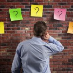 Choice and decisions: businessman thinking with question marks w