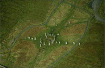 Veduta aerea di Callanish. Il cerchio di pietre ha un diametro di 13 metri, e mostra un lungo viale in direzione nord-sud (il sud è dove si trova il cerchio). La conformazione a croce permette di individuare anche gli altri punti cardinali. Crediti: RCAHMS (Aerial Photography Collection)